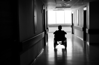 A man in a wheelchair, sitting alone in the middle of a dark nursing home or hospital corridor