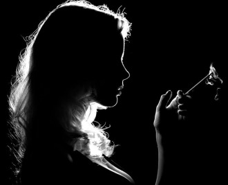 A silhouetted woman in profile holding a cigarette